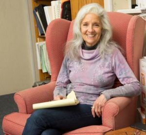 susan smiling sitting in an armchair