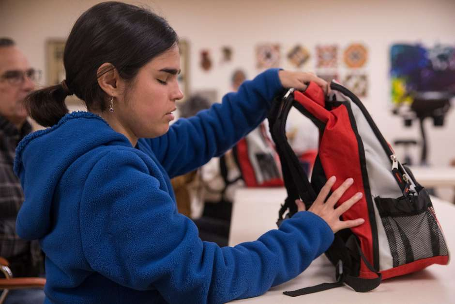 Maycie Vorreiter feels around an emergency-kit backpack, provided during a fire safety train ing session for the blind at the Earle Baum Center in Santa Rosa, to familiarize herself with it.