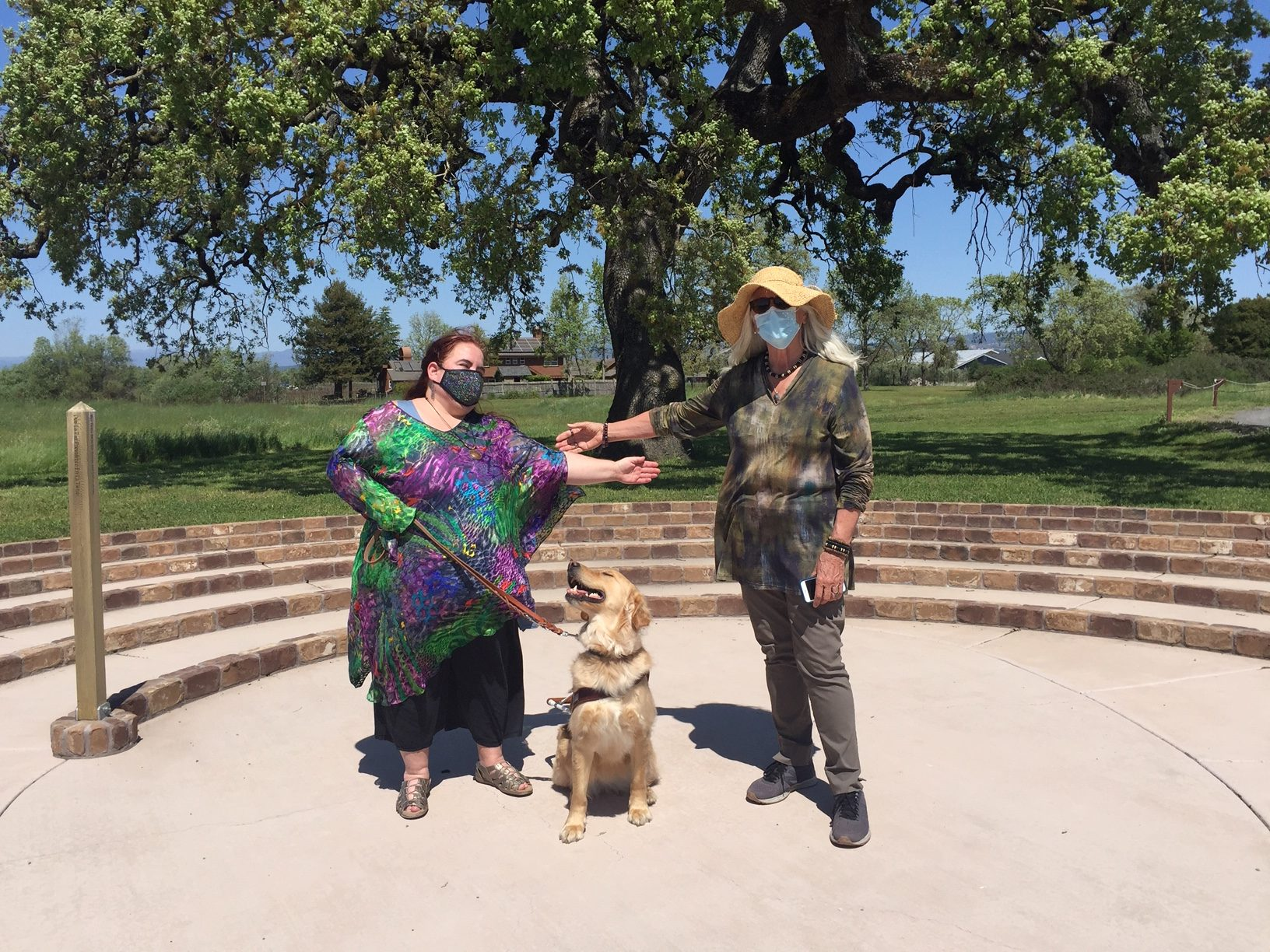 daylight photo in the center of the labyrinth with Maia Scott and her guide dog Gleam and Patricia Jefferson